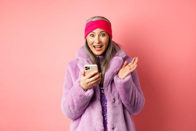 Concept de magasinage et de mode en ligne. femme d'âge mûr asiatique à la recherche d'excité comme la vérification de l'offre promotionnelle internet sur smartphone sur rose