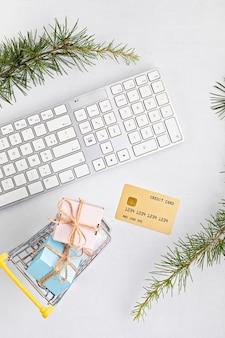 Concept de magasinage de noël en ligne avec coffrets cadeaux, clavier et carte de crédit dorée. vue de dessus, pose à plat