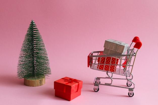 Concept de magasinage de noël panier d'épicerie avec des cadeaux et des jouets d'arbre de noël sur rose