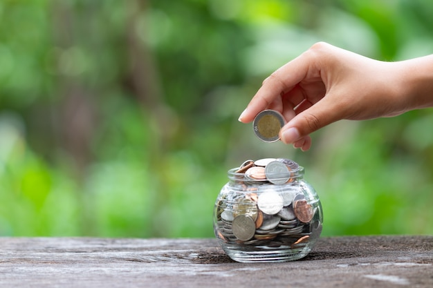 Le concept de main et de pièces économise de l'argent pour la maison,