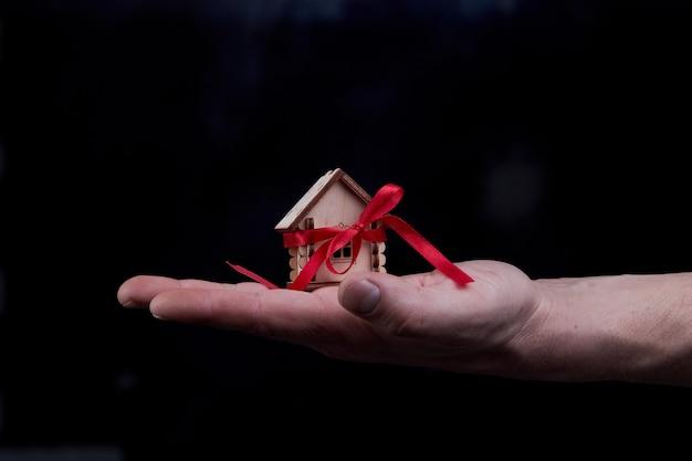 Concept de maison d'hypothèque avec ruban rouge en main sur fond noir