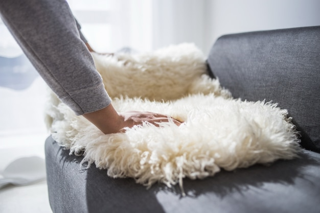Concept maison, immobilier et meuble - décoration masculine nouvelle maison - pose de tapis en peau de mouton sur canapé