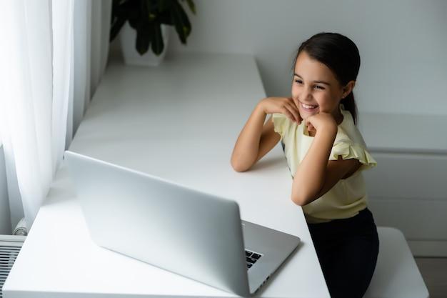 Concept de maison, de loisirs, de technologie et d'internet - petite étudiante avec un ordinateur portable à la maison, petite fille utilise le chat vidéo