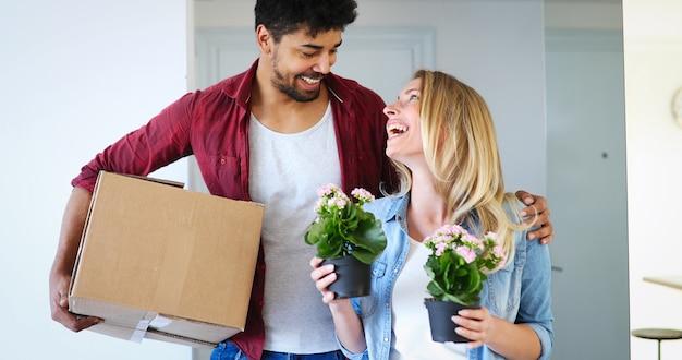 Concept de maison, de personnes, de déménagement et d'immobilier - couple heureux s'amusant en emménageant dans un nouvel appartement