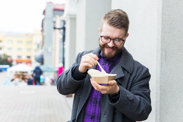 Concept de malbouffe, d'alimentation et de style de vie - un jeune homme avec un repas mange dans la rue de la ville.