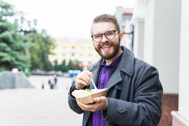 Concept de malbouffe, de nourriture et de mode de vie - jeune homme avec repas mange sur la rue de la ville.