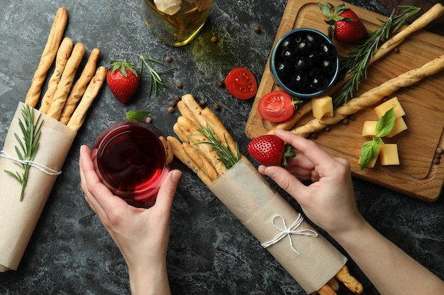 Concept de manger savoureux avec du vin, des bâtonnets de grissini et des collations, vue du dessus