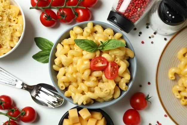 Concept de manger savoureux avec des macaronis au fromage sur fond blanc