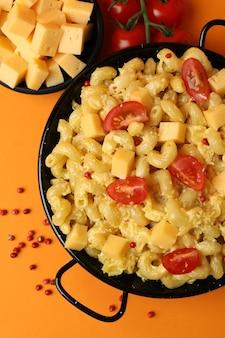 Concept de manger savoureux avec des macaronis au fromage sur fond orange