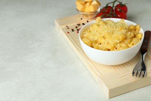 Concept de manger savoureux avec des macaronis au fromage sur une table texturée blanche