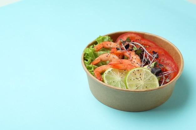 Concept de manger savoureux avec salade de crevettes sur fond bleu