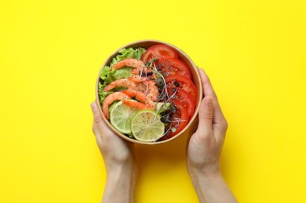 Concept de manger savoureux avec salade de crevettes sur fond jaune