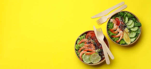 Concept de manger savoureux avec des salades de crevettes sur fond jaune