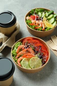 Concept de manger savoureux avec des salades de crevettes sur une table grise