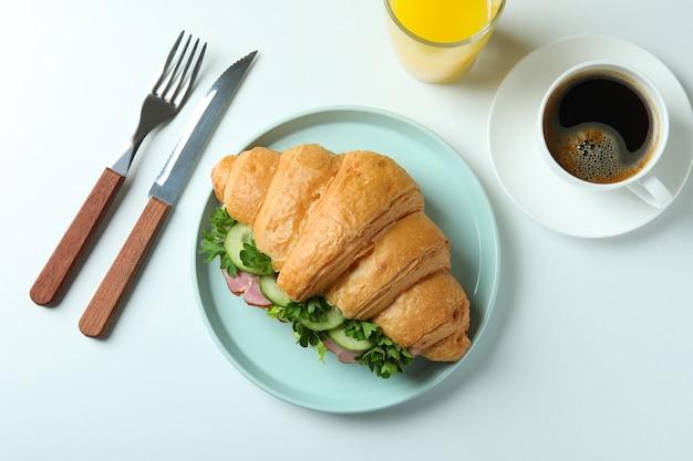 Concept de manger savoureux avec sandwich croissant sur blanc