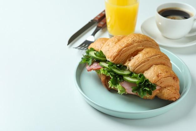 Concept de manger savoureux avec un sandwich croissant sur blanc