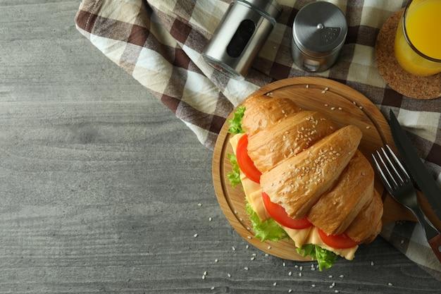 Concept de manger savoureux avec un sandwich croissant sur une table texturée grise