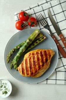 Concept de manger savoureux avec de la viande de poulet grillée sur une table texturée blanche