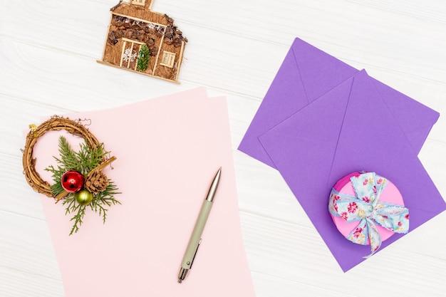 Concept de maquette de vacances d'hiver. la feuille de papier vierge sur une table en bois blanc avec un stylo et des enveloppes