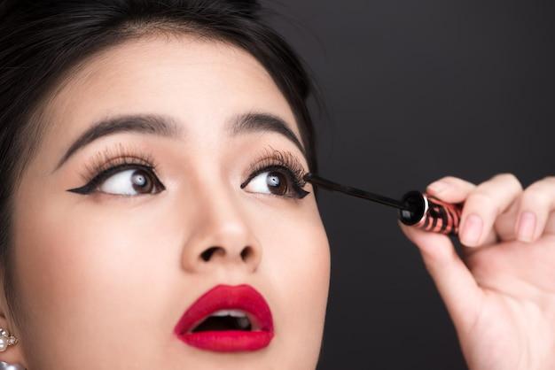Concept de maquillage et de cosmétiques. femme asiatique faisant son mascara noir de cils de maquillage.