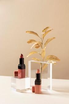 Concept de maquillage avec des rouges à lèvres et des feuilles