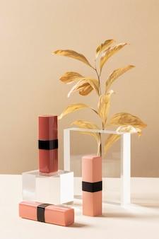 Concept de maquillage avec des rouges à lèvres et des plantes