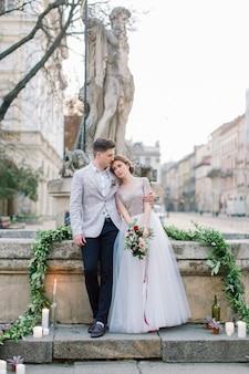 Concept de mariage. le couple de mariage romantique heureux se tient sur les escaliers en pierre en face des bâtiments de la vieille ville. marié romantique et mariée amoureuse embrassant. lviv, ukraine