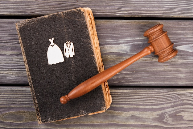 Concept de mariage ou de divorce. vieux livre de droit usé avec vue de dessus de marteau.