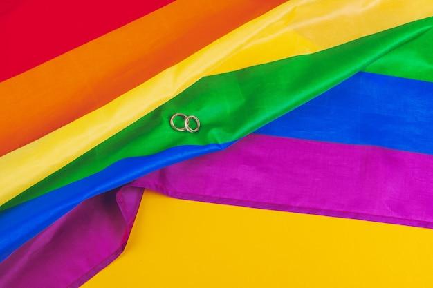 Concept de mariage gay avec drapeau arc-en-ciel et anneaux