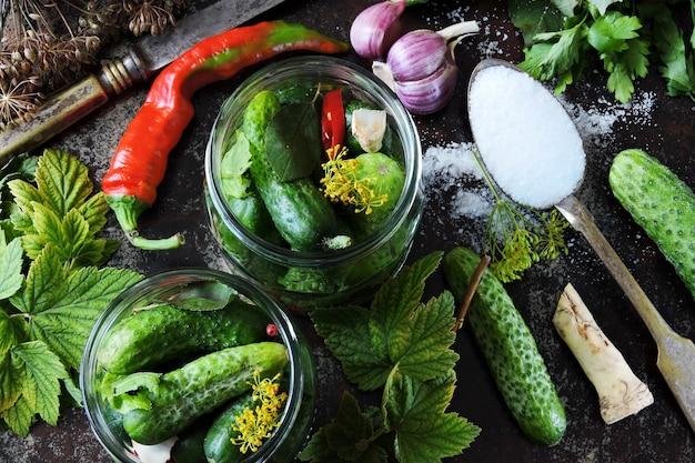 Concept de marinage de concombre avec des pots de concombres, d'herbes et d'épices