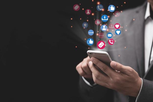 Concept de marketing et de médias sociaux avec homme d'affaires détenant un smartphone