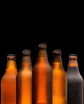 Concept de marque et de marketing pour la bière avec une ligne de bouteilles brunes pleines non marquées non ouvertes sur un fond sombre et sombre conceptuel de l'oktoberfest ou de la vie nocturne