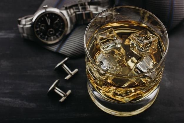 Concept masculin pour la fête des pères. cravate, montres, boutons de manchette et un verre de whisky avec de la glace