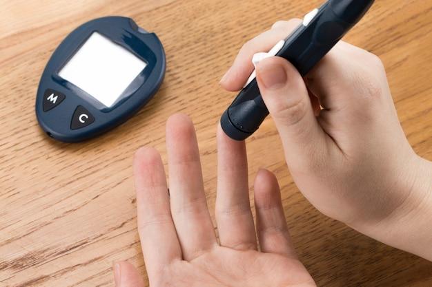 Concept de médecine, diabète, glycémie, soins de santé et personnes. close up of man contrôle la glycémie par glucomètre et bandelette de test à la maison