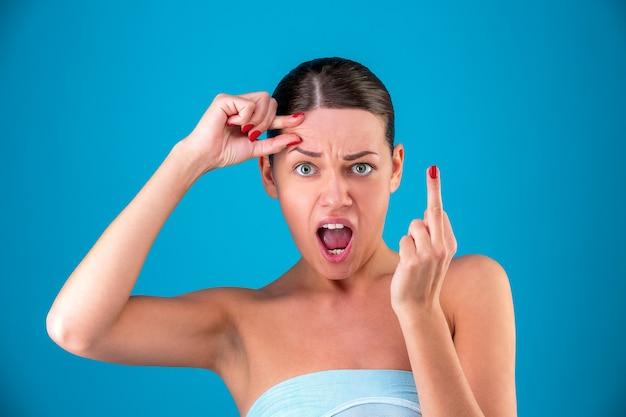 Concept de médecine esthétique. belle fille aux cheveux noirs sur fond bleu, front plissé, montrant la main