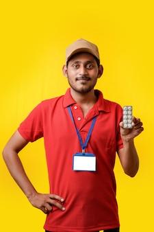 Concept de médecine en ligne : livreur indien tenant la bande de médecine à la main