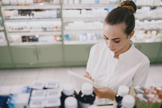 Concept de médecine, pharmaceutique, soins de santé et personnes. pharmacienne prenant des médicaments sur l'étagère.