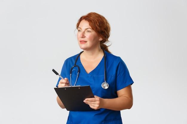 Concept de médecine, de soins de santé et de coronavirus. femme médecin ciblée prenant des notes, examen du patient, écoute des plaintes des personnes à la clinique, écriture du presse-papiers, debout dans des gommages.