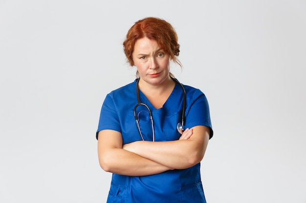 Concept de médecine, de soins de santé et de coronavirus. travailleur médical sceptique et mécontent, médecin regardant avec jugement au patient avec sourcil levé et bras croisés, fond gris debout.