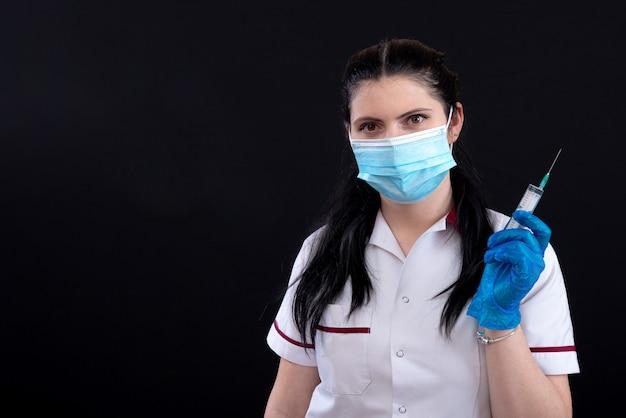 Concept de médecine, de vaccination et de soins de santé, gros plan d'une femme médecin en masque facial avec stéthoscope et seringue sur fond sombre
