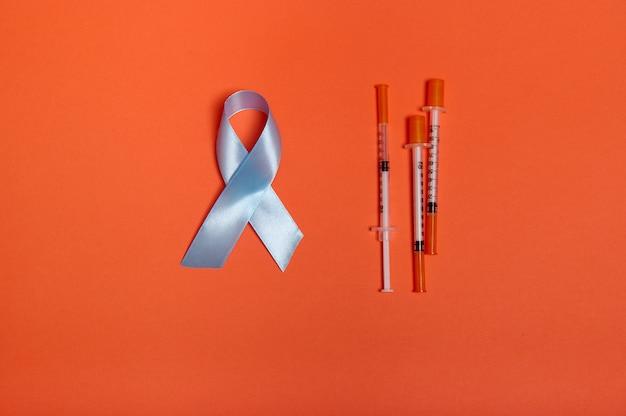 Concept médical 14 pour novembre. mise à plat de seringues à insuline et ruban de satin bleu, couleur de l'arc symbolique de la journée mondiale de sensibilisation au diabète, isolée sur fond orange avec espace de copie pour l'annonce