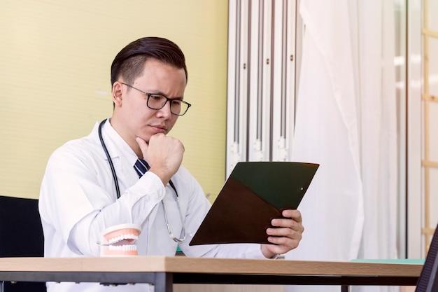 Concept médical; le dentiste lit les résultats de la radiographie dentaire.