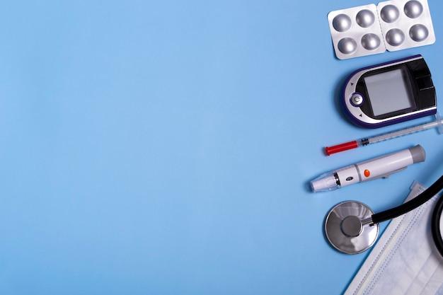 Concept médical sur fond bleu stéthoscope, stylo lancette, glucomètre, masque et pilules. close up copy space concept de diabète. disposition plate.