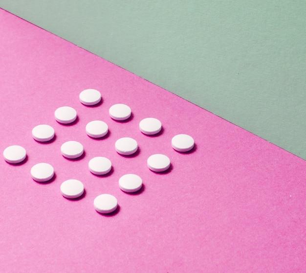 Concept médical minimaliste. groupe de comprimés blancs identiques sur un fond de couleur pastel. vue de dessus