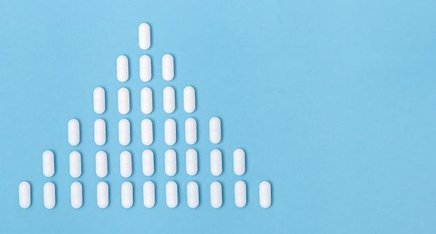 Concept médical, pharmacie et soins de santé. augmentation du nombre de cas dans la population. pilules de médecine pharmaceutique sur fond de couleur bleue avec espace de copie.
