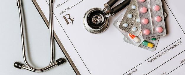 Concept médical à plat avec stéthoscope, pilules, bloc-notes sur le bureau du médecin