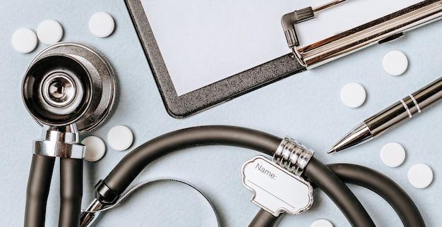 Concept médical à plat avec stéthoscope, pilules, bloc-notes, stylo sur le bureau du médecin