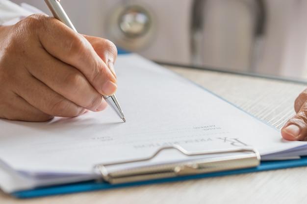 Concept médical de soins de santé, mains du médecin écrit et travaille sur le presse-papiers de prescription w