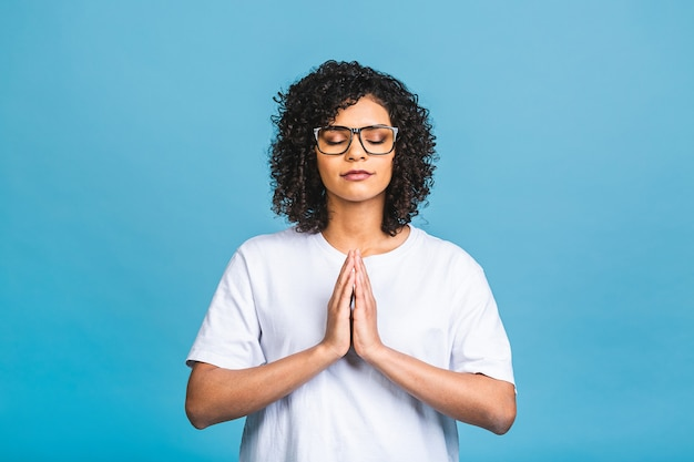Concept de méditation. belle jeune femme afro-américaine se tient dans une pose méditative, bénéficie d'une atmosphère paisible