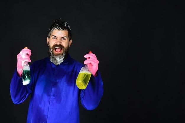 Concept de ménage de nettoyage homme du service de nettoyage professionnel homme barbu gai en uniforme